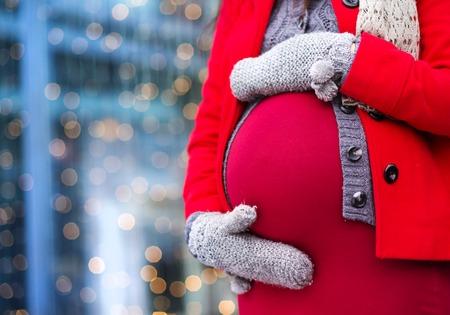 donna innamorata: Particolare del ventre irriconoscibile della donna incinta in inverno al di fuori dei negozi