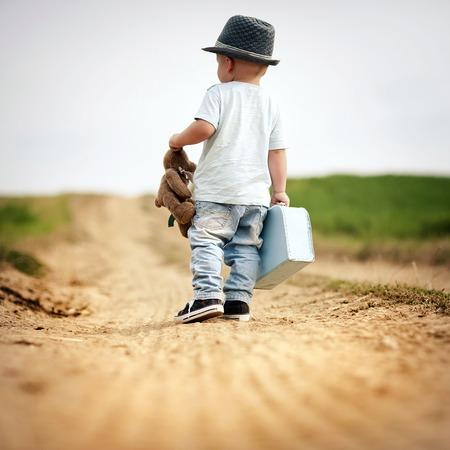 bebes lindos: Vista trasera de niño caminando en el sendero en el campo con suitacase y oso de peluche Foto de archivo