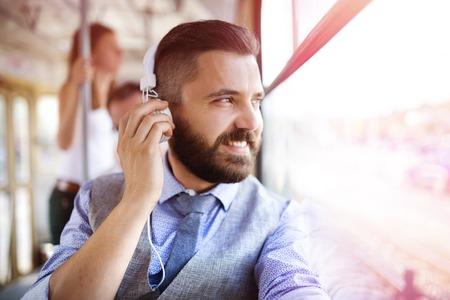 personas escuchando: Inconformista guapo hombre moderno con auriculares que viajan en tranvía en la ciudad