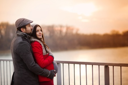 winter day: Young pregnant couple portrait in winter town