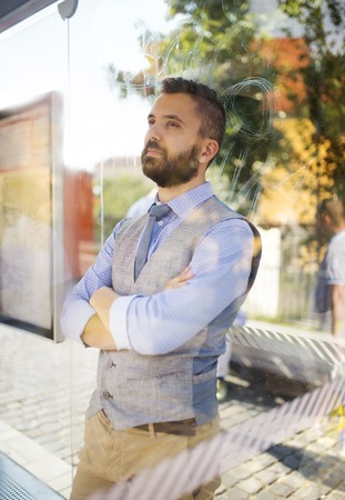 Handsome hipster modern man waiting for bus on bus stop photo