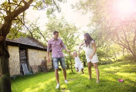 Famille enceinte heureuse se amuser dans le jardin près de la vieille ferme Banque d'images