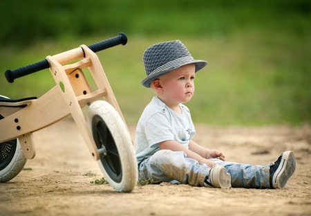 tricycle: Little boy with wooden tricycle in nature