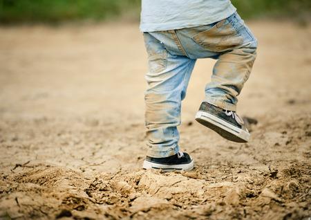 Detail of little boys legs walking in muddy footpath in nature