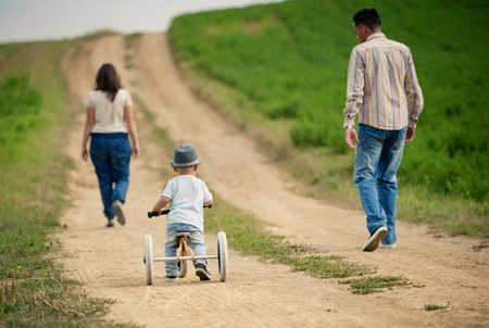 healthy path: Happy family with little boy on wooden tricycle walking in ntaure Stock Photo