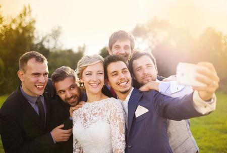 結婚式: 新郎と彼の友人 selfie を取ると美しい若い花嫁の屋外のポートレート