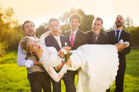 Outdoor portrait of young groom with his friends holding beautiful bride photo