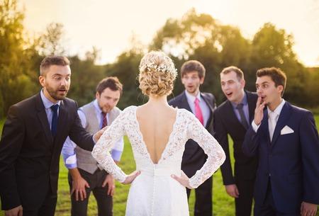Portrait of surprised groomsmen looking at beautiful bride outside photo
