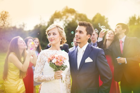 Young newlyweds enjoying romantic moment together at wedding reception outside, wedding guests in background blowing bubbles photo