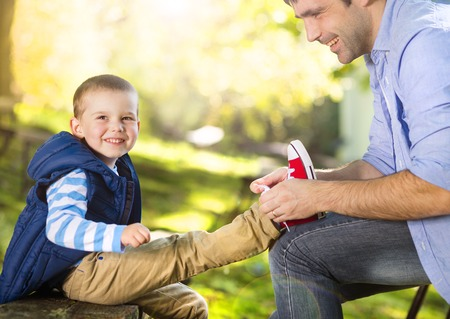 tying: Father is helping his son to tie his shoes in summer nature