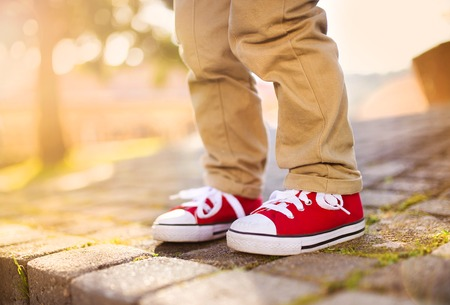 one little boy: Close-up of little boy standing on tiled pavement in summer park Stock Photo