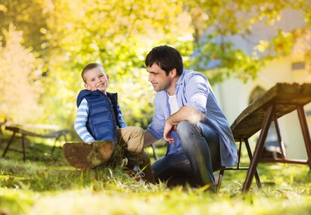 Father and son spending time together in summer nature, little boy is tying his fathers shoes photo