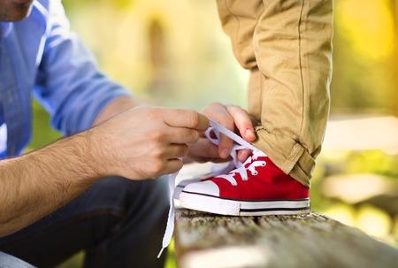 Padre está ayudando a su hijo a atarse los zapatos en la naturaleza verano Foto de archivo - 32527631