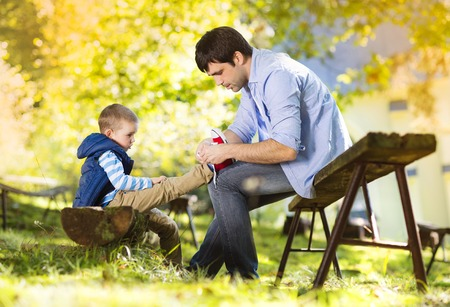 day care: Father and son spending time together in summer nature, little boy is tying his fathers shoes