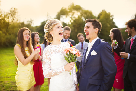 Young newlyweds enjoying romantic moment together at wedding reception outside, wedding guests in background blowing bubbles Stock Photo
