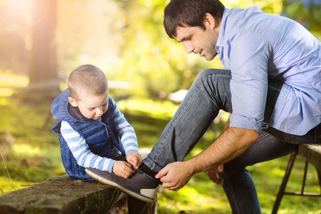 Father and son spending time together in summer nature, little boy is tying his fathers shoes
