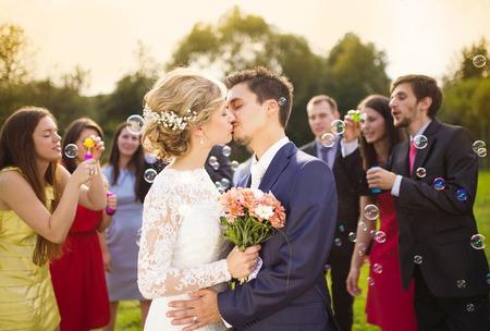 Jóvenes recién casados ??besándose y disfrutando momento romántico juntos en la boda fuera, invitados a la boda en fondo soplando burbujas