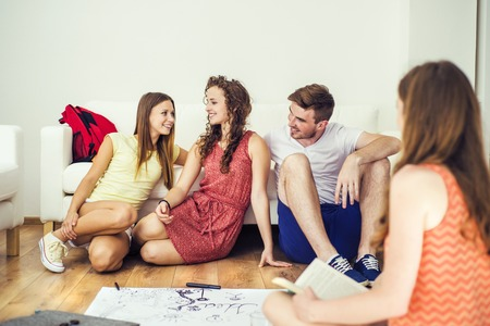 Group of young students studying together and preparing for exams in home interior photo
