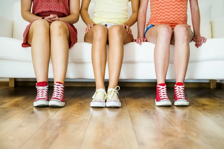 red sofa: Three young girls sitting on sofa, closup on legs and sneakers