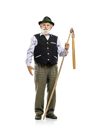 flail: Old bearded bavarian man in hat holding flail in his hand, isolated on white background
