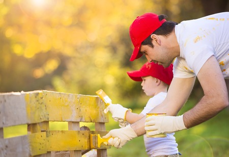 happy day: Cute little boy and his father in red caps painting wooden fence together on sunny day in nature