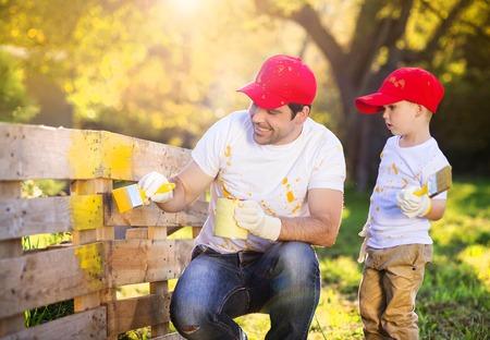 hombre pintando: Ni�o peque�o lindo y su padre en las tapas rojas que pintan cerca de madera juntos en un d�a soleado en la naturaleza