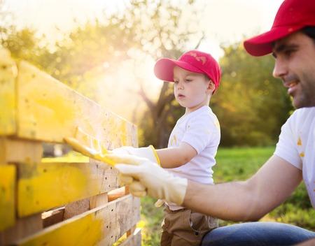Schattige kleine jongen en zijn vader in rode kappen schilderen houten hek bij elkaar op een zonnige dag in de natuur