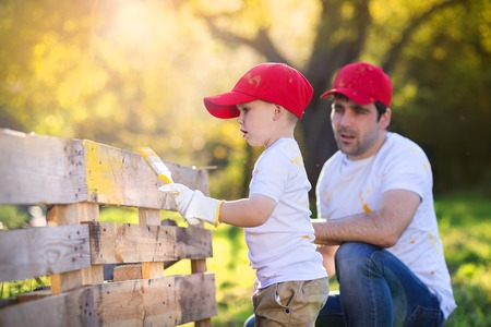 fathers: Cute little boy and his father in red caps painting wooden fence together on sunny day in nature