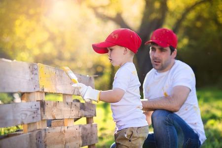 fathers: Ni�o peque�o lindo y su padre de gorras rojas que pintan cerca de madera juntos en un d�a soleado en la naturaleza