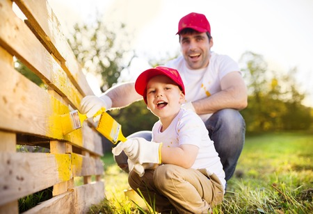 brush paint: Cute little boy and his father in red caps painting wooden fence together on sunny day in nature
