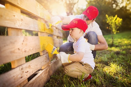 kids painting: Cute little boy and his father in red caps painting wooden fence together on sunny day in nature