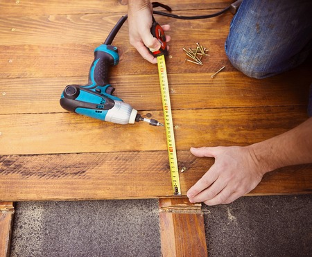 Close up of male hands measuring wood flooring with tape measure 版權商用圖片