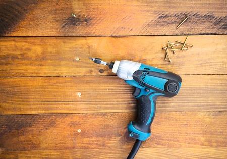 Close-up elektrische boor en nagels links op houten vloer Stockfoto