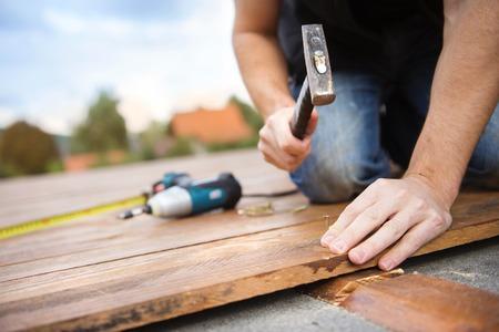 menuisier: Handyman installation de parquet dans le patio, en travaillant avec un marteau