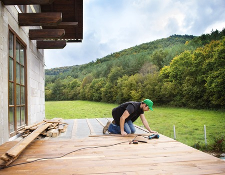 Handyman installing wooden flooring in patio, working with drilling machine