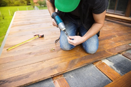 drill floor: Handyman installing wooden flooring in patio, working with drilling machine