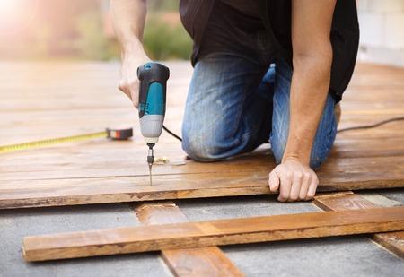 carpintero: Manitas instalaci�n de suelos de madera en el patio, que trabaja con la perforadora Foto de archivo