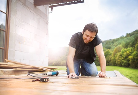 Smiling handyman installing wooden flooring in patio, working with hammer