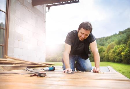 Lächelnd Handyman Installation Holzboden im Innenhof, der mit Hammer arbeitet Standard-Bild - 32857474