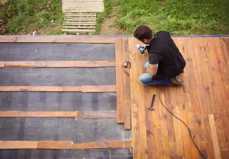 Handyman installing wooden flooring in patio, working with drilling machine Stok Fotoğraf - 32857477