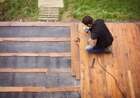 Klusjes man houten vloer in de patio, het werken met boormachine