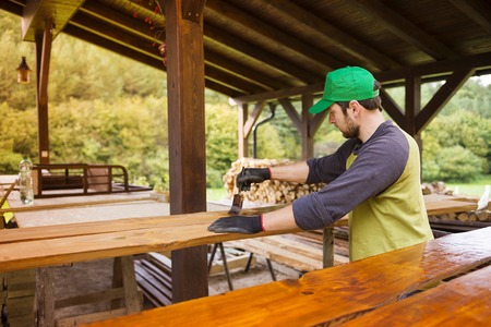 hombre pintando: Manitas de pino barnizado tablones de madera en el patio fuera de la nueva casa