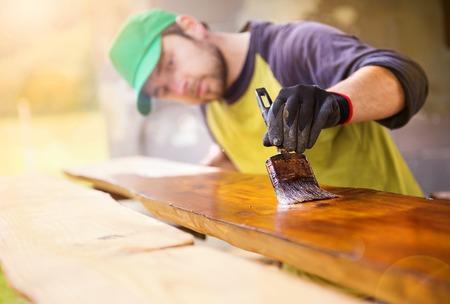 便利屋の新しい家の外のパティオで松の木の板のニスを塗る