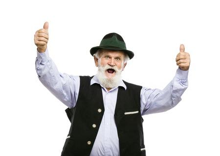 bigote: Retrato de anciano con barba en el sombrero bávaro tradicional con los pulgares para arriba aislados en fondo blanco