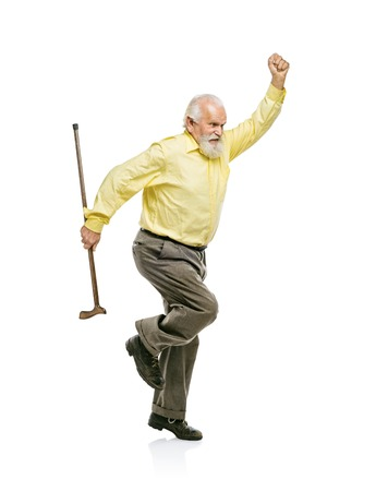 Happy old active bearded man jumping with cane in his hand isolated on white background
