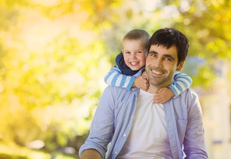 Father and son spending time together in sunny nature, son is hugging father photo