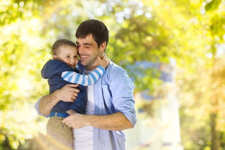 Father and son spending time together hugging in sunny nature photo