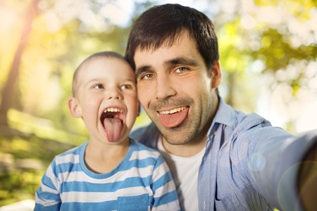 Father and son spending time together in sunny nature, taking selfies and making grimaces photo