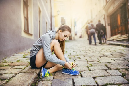 Young female runner is tying her running shoes on tiled pavement in old city center photo