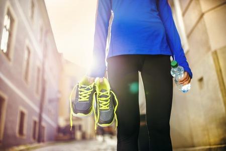 Onherkenbaar vrouwelijke agent die haar loopschoenen en een fles water in het oude stadscentrum